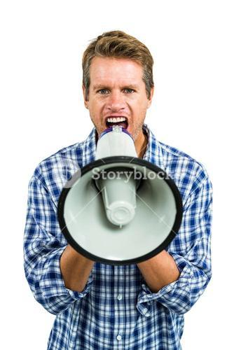 Portrait of angry man shouting through megaphone