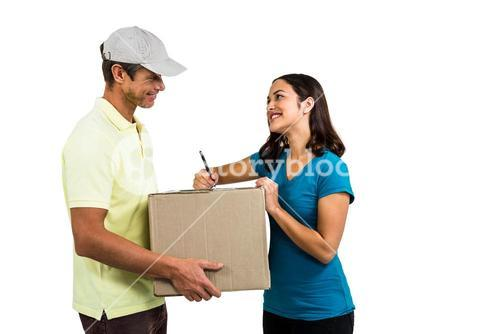 Smiling woman with delivery man holding cardboard box