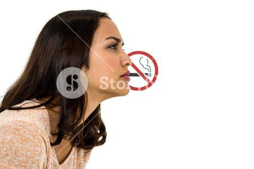 Serious woman looking away with no smoking sign