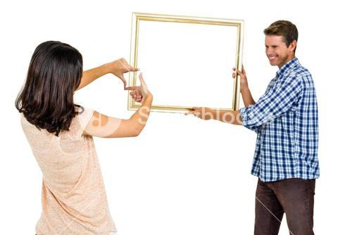 Happy young couple hanging picture frame