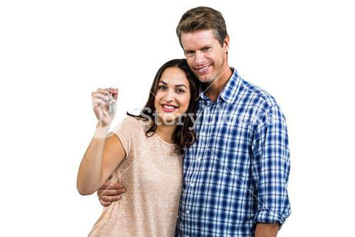 Portrait of happy couple embracing while holding keys