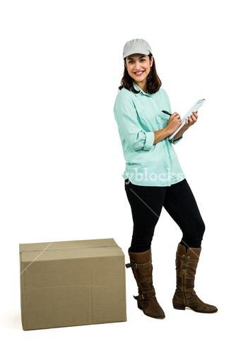 Happy delivery woman with clipboard standing by box