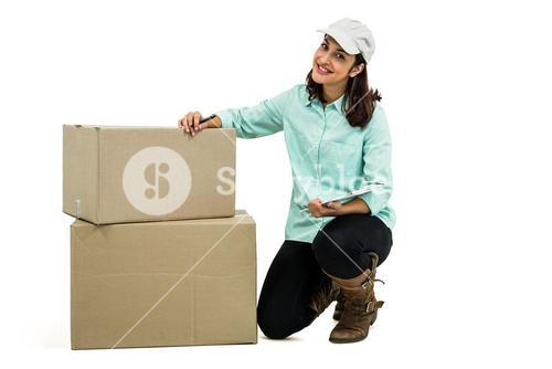 Delivery woman with clipboard kneeling by box
