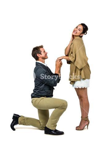 Man proposing woman while kneeling and holding hands