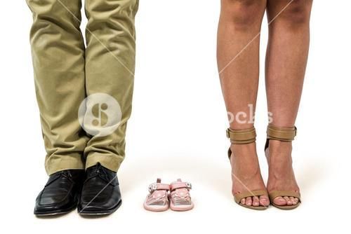 Low section of man and woman amidst baby shoes