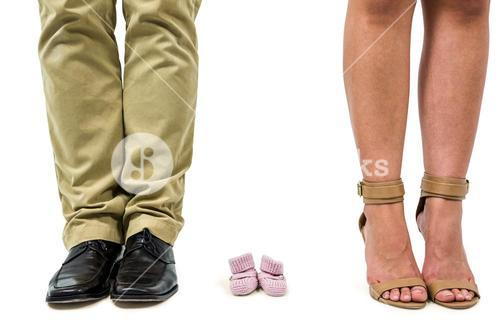 Close-up of man and woman amidst baby shoes