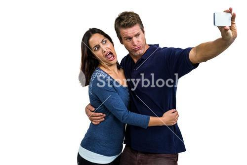 Young couple making face while taking selfie