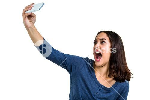 Young woman making face while taking selfie