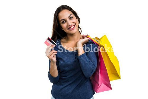 Portrait of happy young woman with shopping bags and payment card