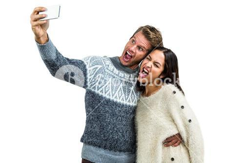 Couple making face while taking selfie