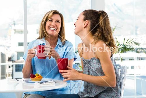 Mother and daughter eat breakfast