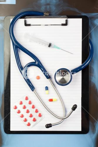 Note pad and blister strip with medicine and blue stethoscope