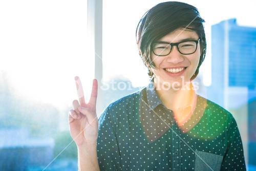 Smiling hipster businessman doing peace sign