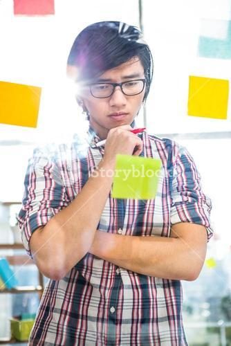 Creative businessman writing on sticky notes
