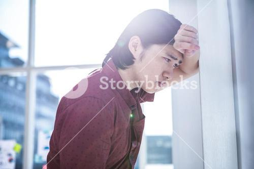 Worried creative businessman leaning on wall