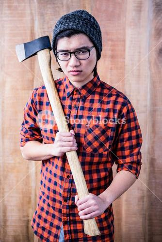 Serious hipster holding a axe