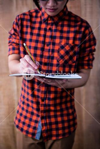 Hipster taking notes on notebooks