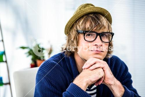 Thoughtful hipster businessman looking at the camera