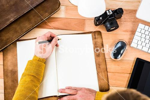 Above view of man writing on notebook