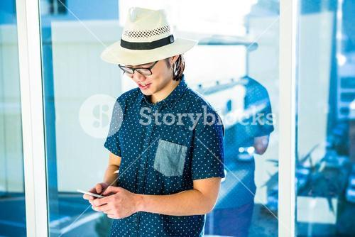 Smiling hipster businessman texting