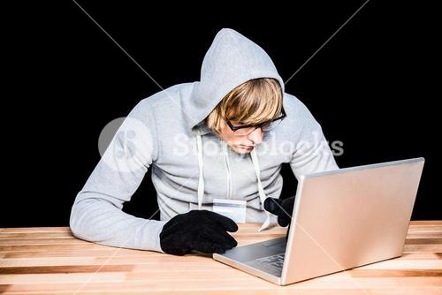 Man in hood jacket hacking a laptop