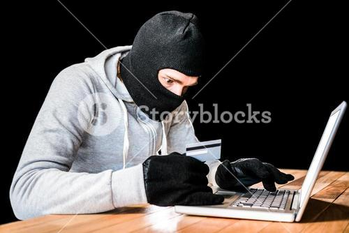 Focused thief with hood typing on laptop