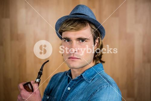 Serious hipster holding pipe