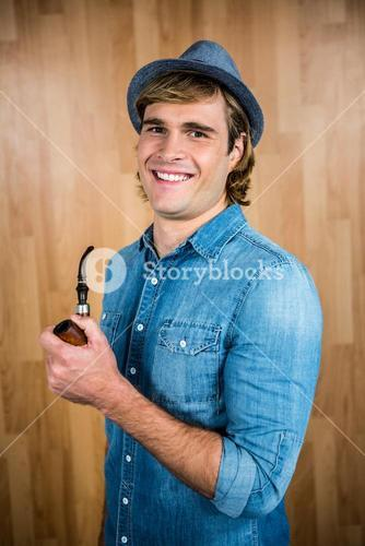 Cheerful hipster holding pipe