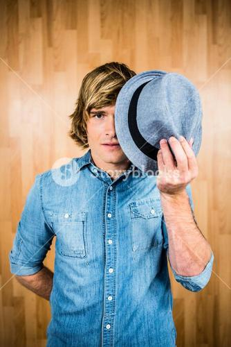 Focused hipster man hiding his face