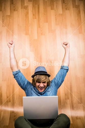 Cheerful blond hipster looking at laptop