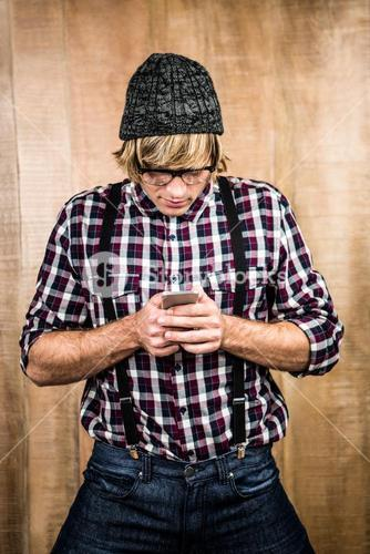 Focused blond hipster holding smartphone