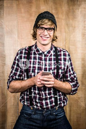 Smiling blond hipster holding smartphone