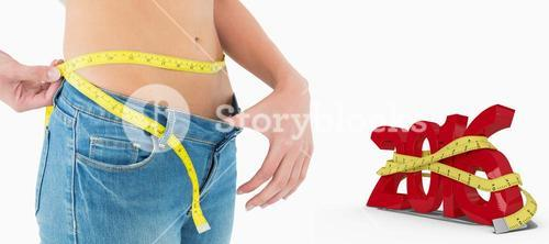 Composite image of mid section of woman measuring waist in a big sized jeans