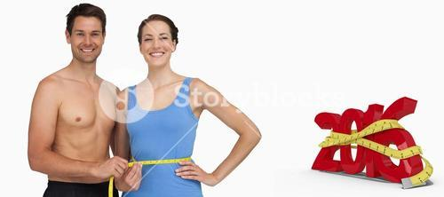 Composite image of fit young man measuring womans waist