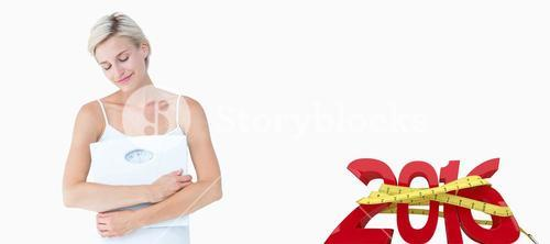 Composite image of happy woman holding scales