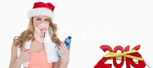 Composite image of festive fit blonde holding bottle of water