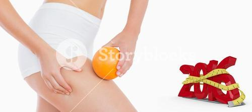 Composite image of woman squeezing fat on thigh as she holds orange