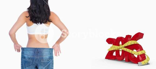 Composite image of back of woman holding her too big jeans