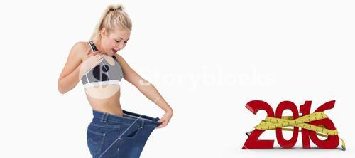 Composite image of young thin woman wearing old pants after losing weight