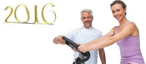 Composite image of portrait of a happy woman on stationary bike with trainer