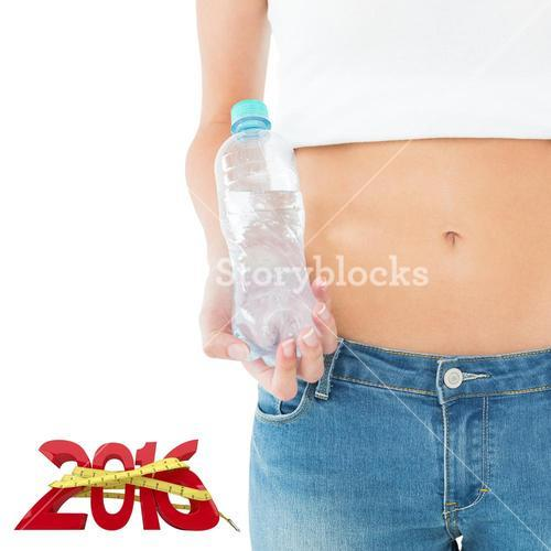 Composite image of mid section of a fit woman holding a bottle of water