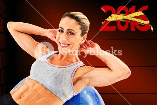 Composite image of fit woman doing sit ups on blue exercise ball smiling at camera
