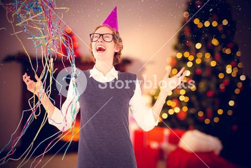 Composite image of happy geeky hipster wearing a party hat