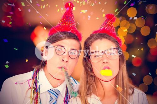 Composite image of geeky hipster wearing a party hat with blowing party horn