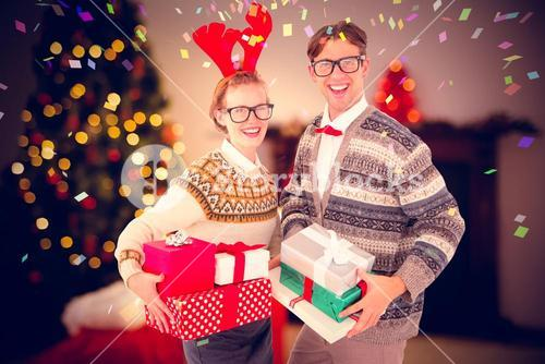 Composite image of smiling woman wearing red reindeer horn and holding gifts with man