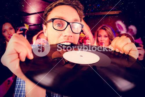 Composite image of geeky hipster biting vinyl record