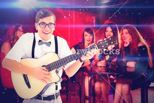 Composite image of geeky hipster playing guitar and singing