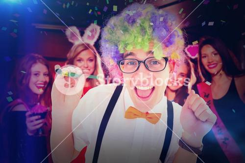 Composite image of geeky hipster wearing a rainbow wig holding party horn