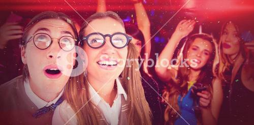 Composite image of geeky hipster couple raising eyes