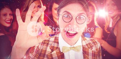 Composite image of geeky hipster doing the ok sign